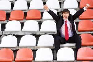 young man in black suit sitting on the audience bleachers